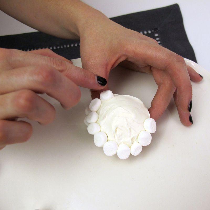 Applying mini marshmallows to baby lamb cupcake design
